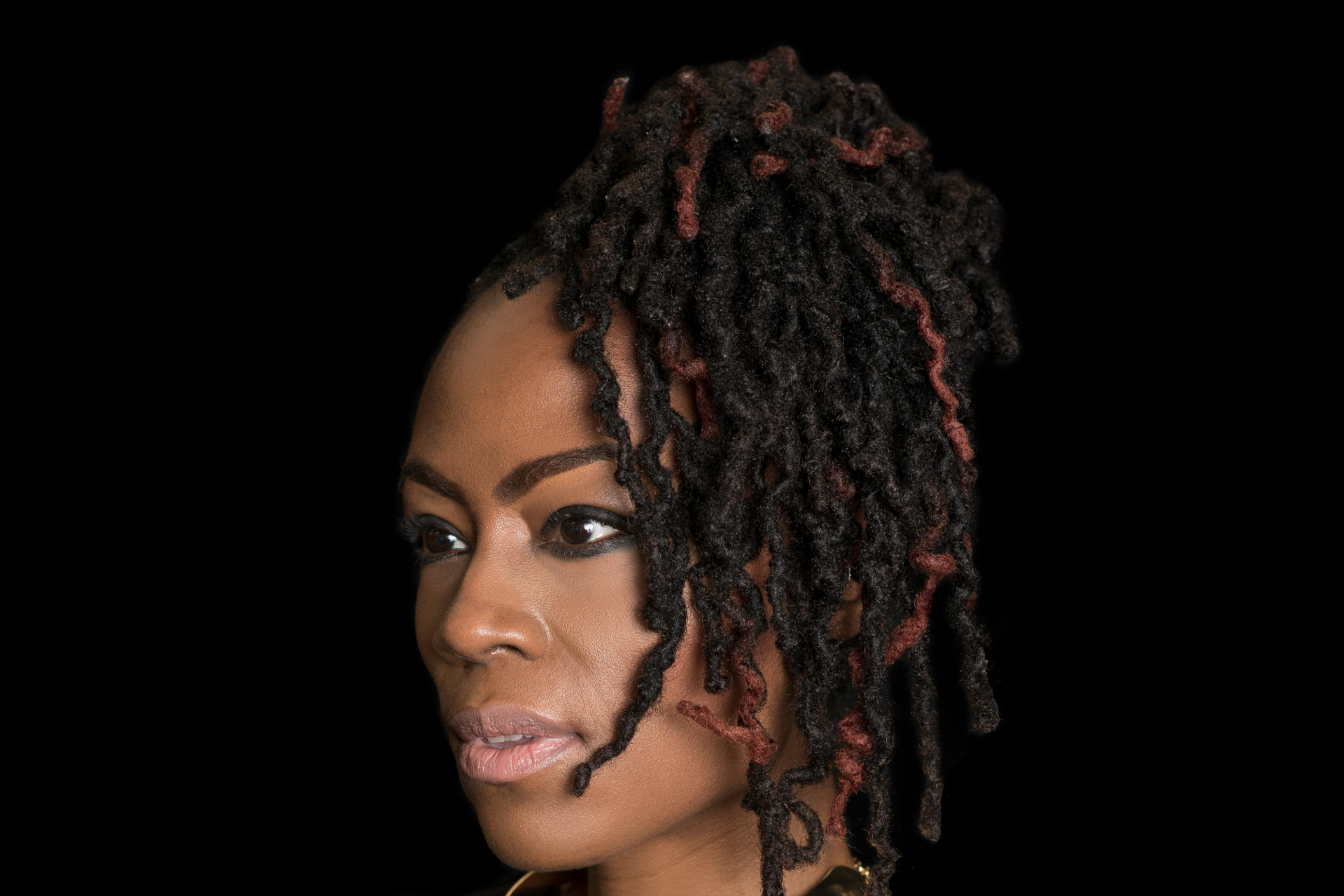 Woman with dreadlocks with highlight colors, gathered in ponytail